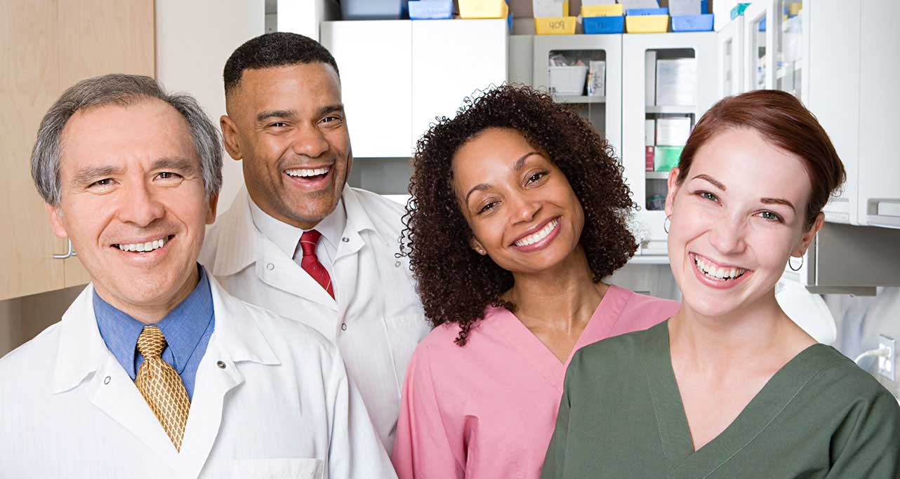 Doctor, pharmacist, and medical team smiling.